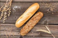 Baguette e grano rustici su una vecchia tavola di legno d'annata Fotografia Stock