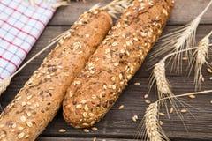 Baguette e grano rustici su una vecchia tavola di legno d'annata Fotografie Stock Libere da Diritti