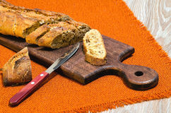 Baguette with flax seed chopped on kitchen Board Royalty Free Stock Photography