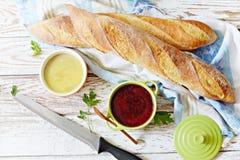Baguette francés curruscante fresco con la coronilla de hígado de pollo y la mermelada de la baya en un fondo envejecido blanco foto de archivo libre de regalías