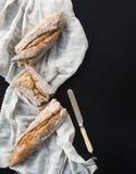 Baguette francés roto en pedazos en una toalla de cocina blanca con Foto de archivo