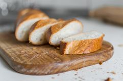 Baguette francês cortado na placa de corte de madeira Pão para o jantar fotos de stock royalty free