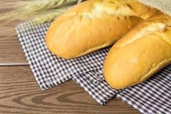 Baguette francesi con il sacco sulla biancheria da tavola Fotografie Stock