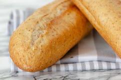 Baguette francesi di recente al forno sulla tavola di legno bianca vista superiore, fotografia stock