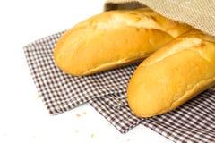 Baguette francesi in sacco su fondo bianco Immagine Stock