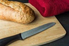 Baguette francesi sul tagliere con il coltello ed il panno di pane Fotografia Stock Libera da Diritti