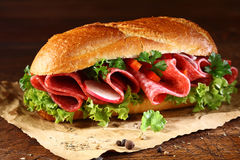 Baguette with fresh lettuce and salami Stock Photo