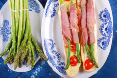 Baguette with green asparagus wrapped in ham Stock Image