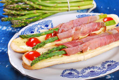 Baguette with green asparagus wrapped in ham Royalty Free Stock Images