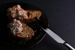 Baguette grillée délicieuse de tranches de pain avec des poissons, des verts, le fromage et la sauce d'un plat noir près du coute Photo stock
