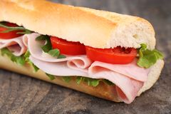 Baguette. With ham, cheese, lettuce and tomatoes royalty free stock image