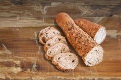 Baguette Integraal Bruin die Brood in Plakken op Oude Houten Lijst wordt gesneden Royalty-vrije Stock Afbeelding