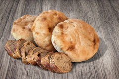 Three Pitta Bread Loaves And Baguette Bread Slices On Porcelain Plate Set On Old Weathered Knotted Picnic Table Grunge Surface Stock Photo