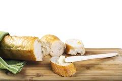 Baguette longo e faca de manteiga de madeira na placa de corte de madeira Fotografia de Stock Royalty Free