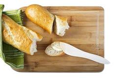 Baguette longo e faca de manteiga de madeira na placa de corte de madeira Imagem de Stock