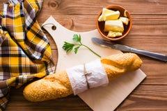 Baguette, mantequilla, cuchillo y perejil en una tabla de cortar Fotos de archivo libres de regalías
