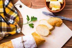 Baguette, mantequilla y perejil cortados en una tabla de cortar Fotos de archivo libres de regalías