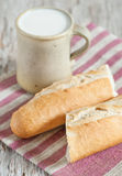 Baguette and milk in ceramic mug on the wooden board Royalty Free Stock Photography
