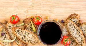 Baguette, olives, glass of vine, peppers and tomatoes, copy spac Royalty Free Stock Images