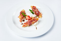 Baguette pieces covered with grilled bacon on plate served luxury. Stock Photography