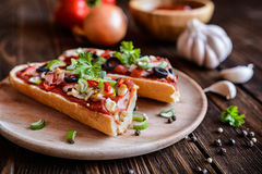 Baguette pizza with bacon, salami, cheese and vegetable Royalty Free Stock Photos