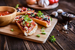Baguette pizza with bacon, salami, cheese and vegetable Royalty Free Stock Image