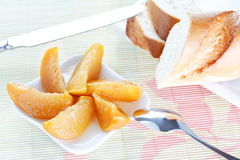 Baguette on plate, peach dessert, spoon and knife Royalty Free Stock Photo