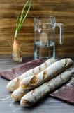 Baguette quatre sur une table en bois Photo stock