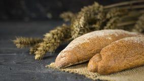 Baguette recién hecho dos de la harina de trigo en un pedazo de arpillera con los oídos en la tabla Imagen de archivo libre de regalías