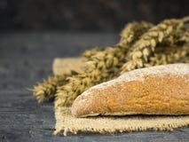 Baguette recién hecho dos de la harina de trigo en un pedazo de arpillera con los oídos en la tabla de madera oscura Imágenes de archivo libres de regalías