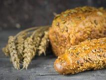 Baguette recién hecho y una barra de pan de la harina de trigo con los oídos del trigo en una tabla rústica Fotografía de archivo libre de regalías