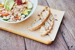 Baguette recientemente cortado junto a una ensalada fresca en el tablero de madera foto de archivo