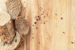 Baguette rye bread sprinkled with various seeds on a wooden board Stock Images