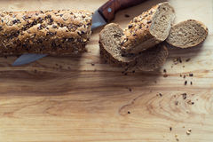 Baguette rye bread sprinkled with various seeds on a wooden board Stock Photo