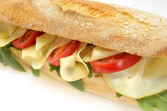 Baguette sandwich. Closeup of a baguette sandwich with ruccola, cheese and tomatoes. Image isolated on white studio background Royalty Free Stock Images