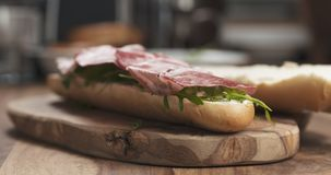Baguette sandwich with coppa and cream cheese on wood board. Wide photo Royalty Free Stock Photography