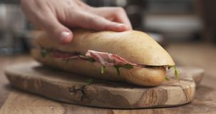 Baguette sandwich with coppa and cream cheese on wood board. Wide photo Stock Photo