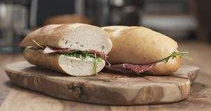 Baguette sandwich with coppa and cream cheese on wood board. Wide photo Stock Image