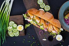 Baguette sandwich with fish, egg, pickled onions and lettuce leaves. royalty free stock photos