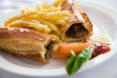 Baguette Sandwich and fries. Plated baguette sandwich and crispy fries Stock Image