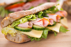 Ham and vegetables sandwich. Baguette sandwich with ham, swiss cheese and cucumber Stock Photos
