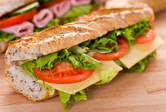 Sandwich with swiss cheese and vegetables. Baguette sandwich with slices of ham, swiss cheese and tomatoes Royalty Free Stock Photo
