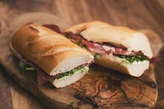 Baguette sandwiches with coppa ham on wood board. Shallow focus Royalty Free Stock Photo