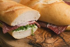 Baguette sandwiches with coppa ham on wood board. Shallow focus Stock Photo