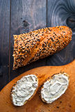 Baguette and sandwiches with creamcheese. Sandwich with cream cheese on cutting board and baguette on rustic wooden background royalty free stock photo