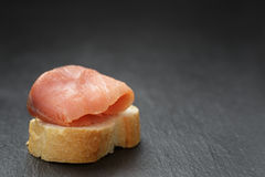 Baguette slice with curred salmon on slate Royalty Free Stock Photos