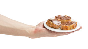 Baguette slices spread with nut-choco paste in man hand Royalty Free Stock Images