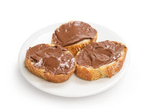 Baguette slices spread with nut-choco paste on plate Stock Image