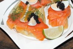 Baguette, smoked salmon, egg, caviar, orange Stock Photography