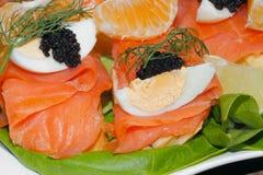 Baguette, smoked salmon, egg, caviar, orange Stock Images